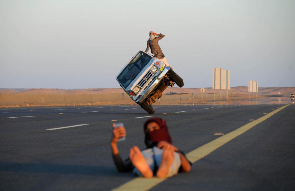 Ein Junge liegt auf dem Boden und macht ein Selfie, während im Hintergrund ein Auto seitlich auf zwei Rädern die Strasse entlang fahrt.