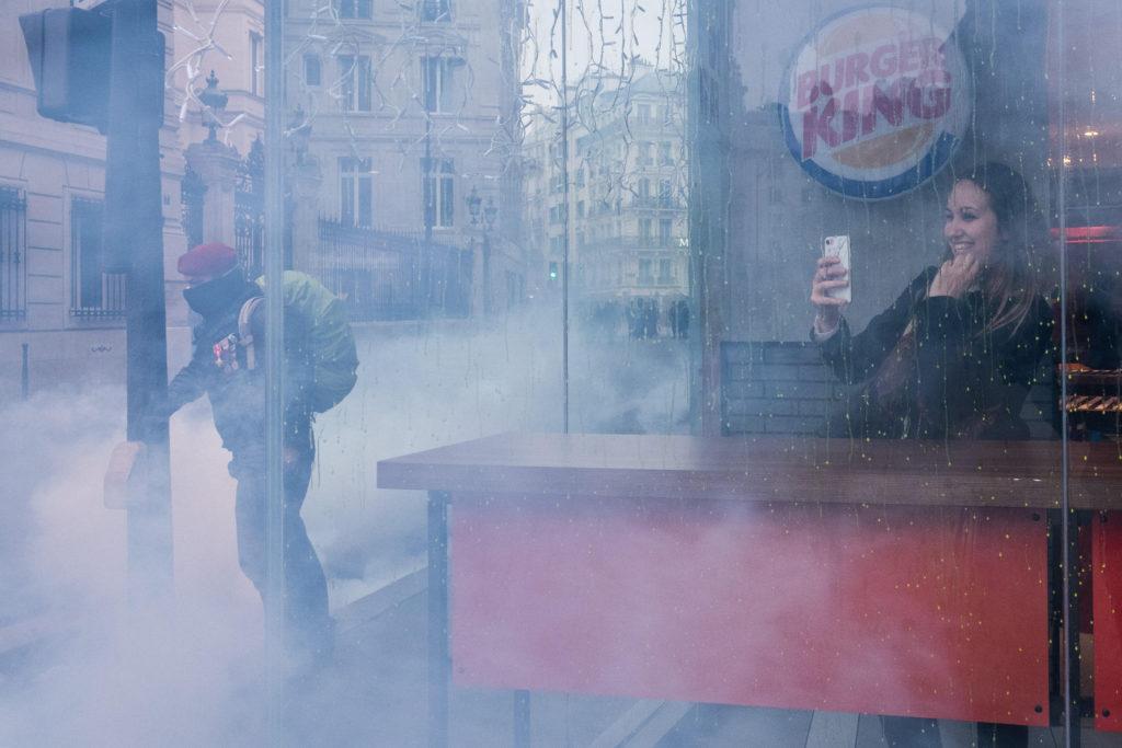 Eine Frau macht in einem Burger King-Restaurant hinter der Scheibe ein Bild, während sich draussen ein Demonstrant den Weg durch den Rauch bahnt.