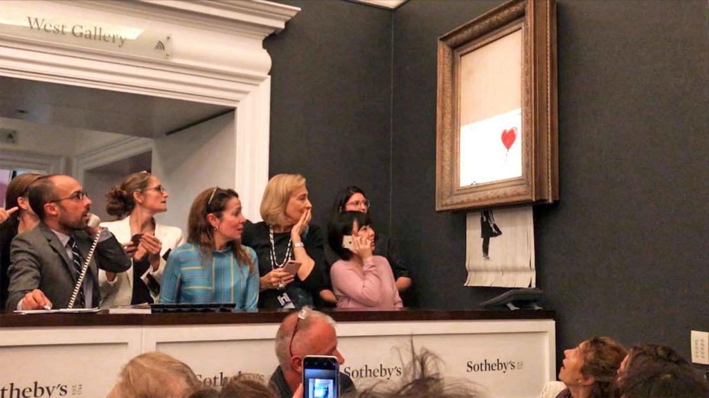 Auktionsteilnehmer beobachten überrascht, wie sich das Bild von Banksy selbst schreddert.