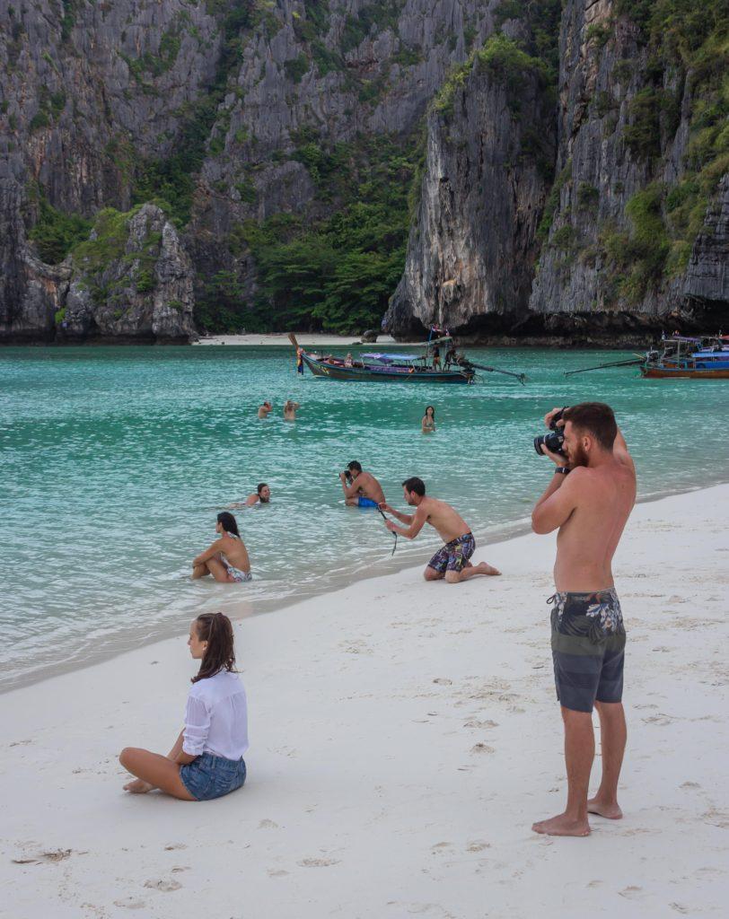Mehrere Frauen posieren hintereinander in einer Bucht, während ihre Partner ein Bild von ihnen machen.