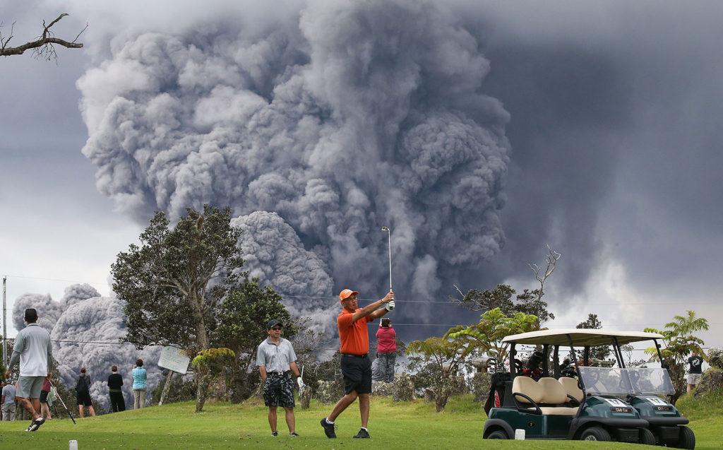 Menschen golfen auf einer grünen Wiese, während im Hintergrund eine grosse Aschewolke aufsteigt.