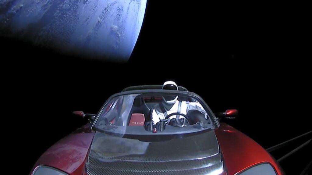Ein Auto mit einem Astronauten am Steuer kreist um die Erde.