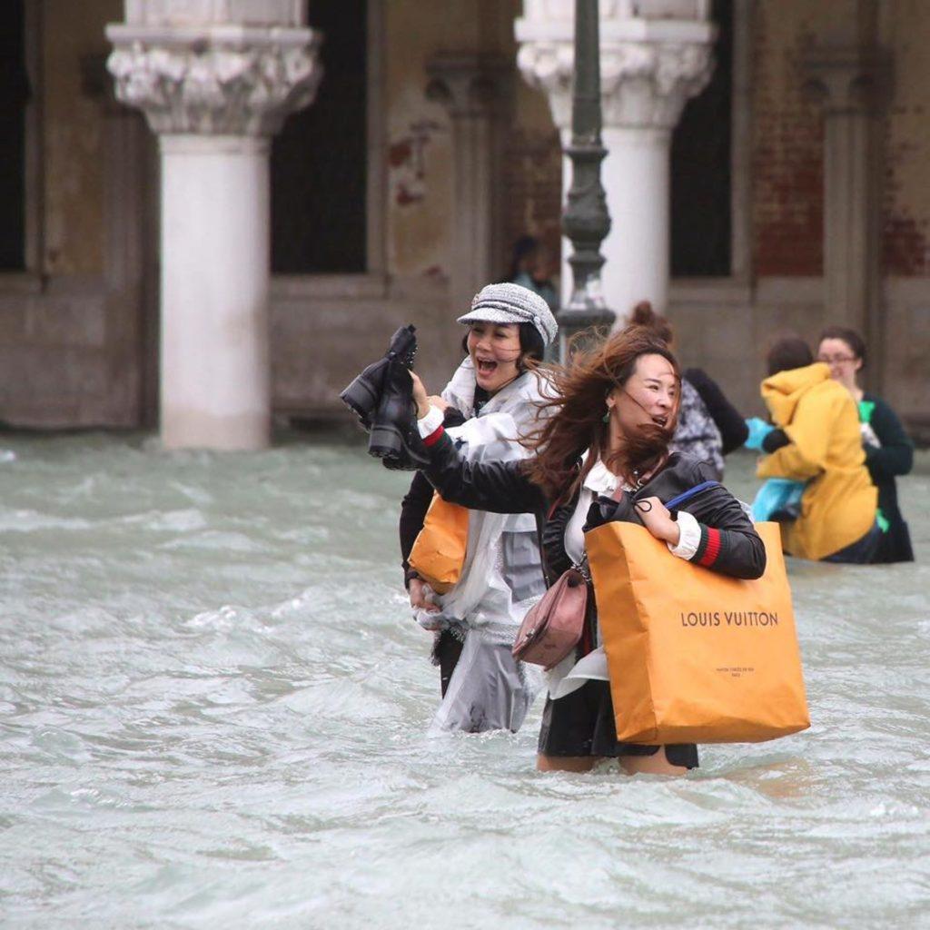 Zwei asiatische Touristinnen retten im Hochwasser von Venedig ihre Einkäufe.